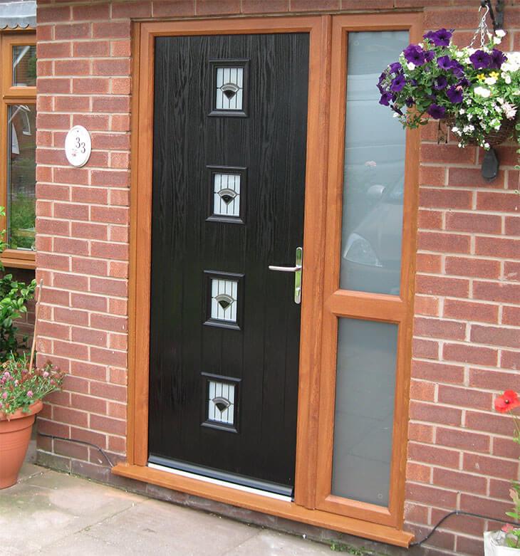Black composite door with an oak effect frame